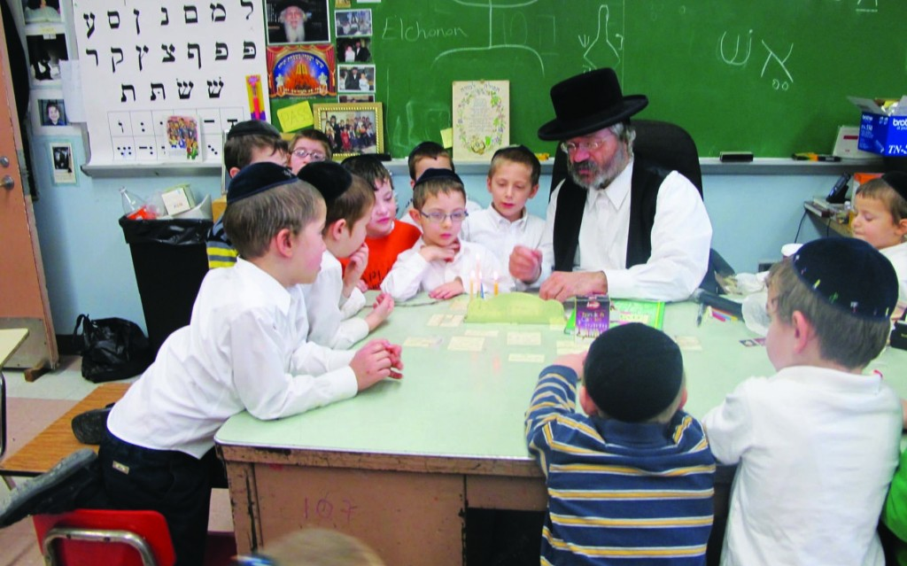 Rabbi Mordechai Jungreis's first-grade class at Yeshivah Chaim Berlin watches as he lights the menorah Sunday. Rabbi Jungreis is Mara d'Asra of the Nikolsburger Shul of Boro Park and the Woodbourne Shul.