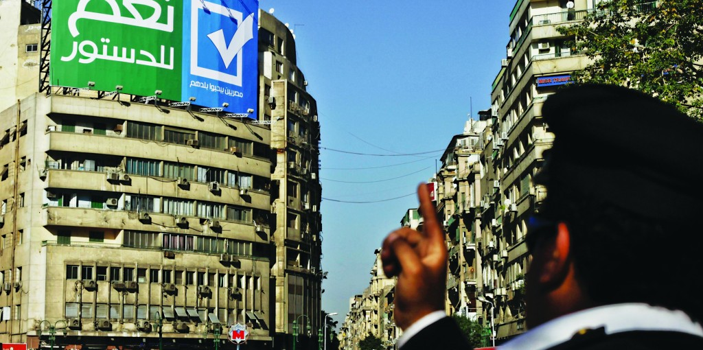 """An Egyptian police major general points toward a sign in Arabic that reads, """"Yes to the constitution; Egyptians love their country,"""" in Tahrir Square, Cairo, Egypt, Wednesday. The constitutional referendum is to be held on Jan. 14 and 15, 2014. (AP Photo/Nariman El-Mofty)"""