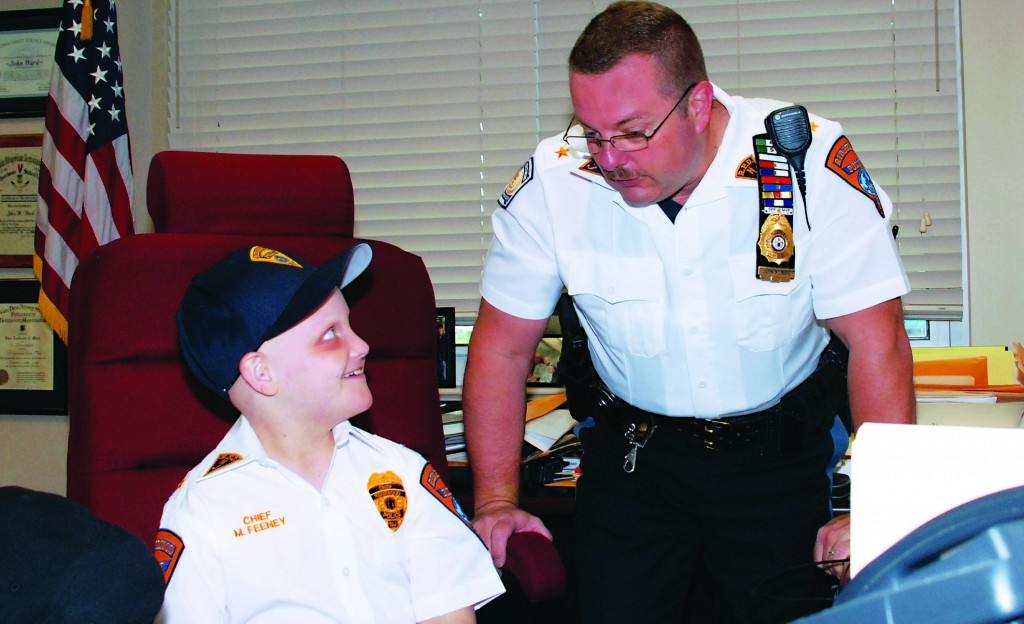 Honorary Ridgewood, N.J., Police Chief Michael Feeney, 10, gets some advice from Ridgewood Police Chief John Ward at the start of the work day on June 14, 2013. (AP Photo/The Record of Bergen County, Marion Brown)