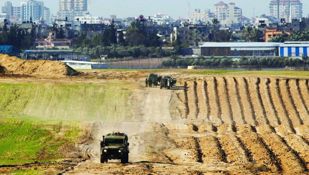 Israeli military jeeps are seen at the scene of a sniper attack near the border with the northern Gaza Strip on Tuesday. (REUTERS/Amir Cohen)