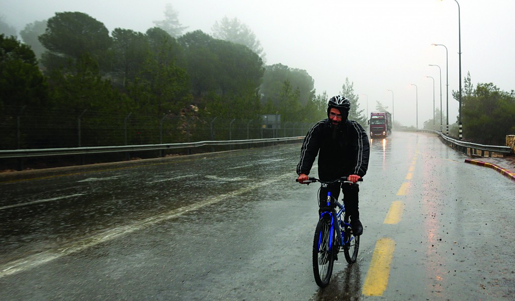A bicycle rider on a rainy, windy winter Wednesday in Yerushalayim. (Nati Shohat/FLASH90)