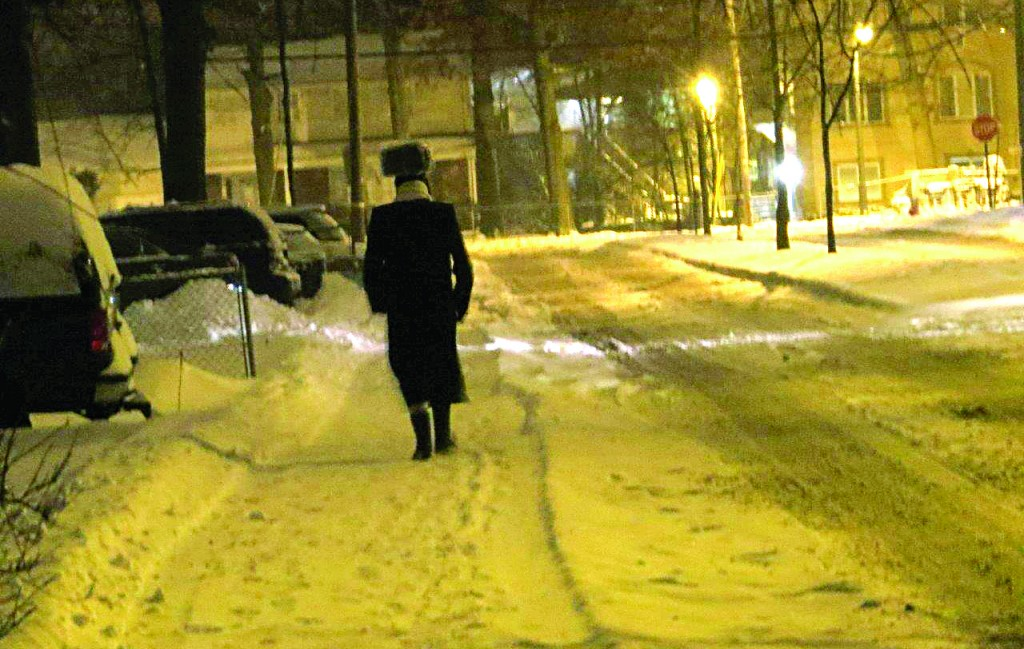 A man walks in Monsey on Motzoei Shabbos during a snowstorm. (JDN)