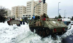 An IDF tank clearing a snow-covered street in Yerushalayim on Sunday. (Meital Cohen/Flash 90)