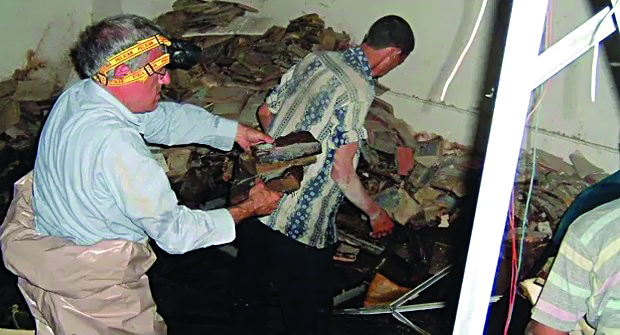 Harold Rhode, a Jewish analyst working with the Coalition Provisional Authority in Baghdad, in the Mukhabarat basement inspecting the damaged sefarim in 2003. (US National Archives)
