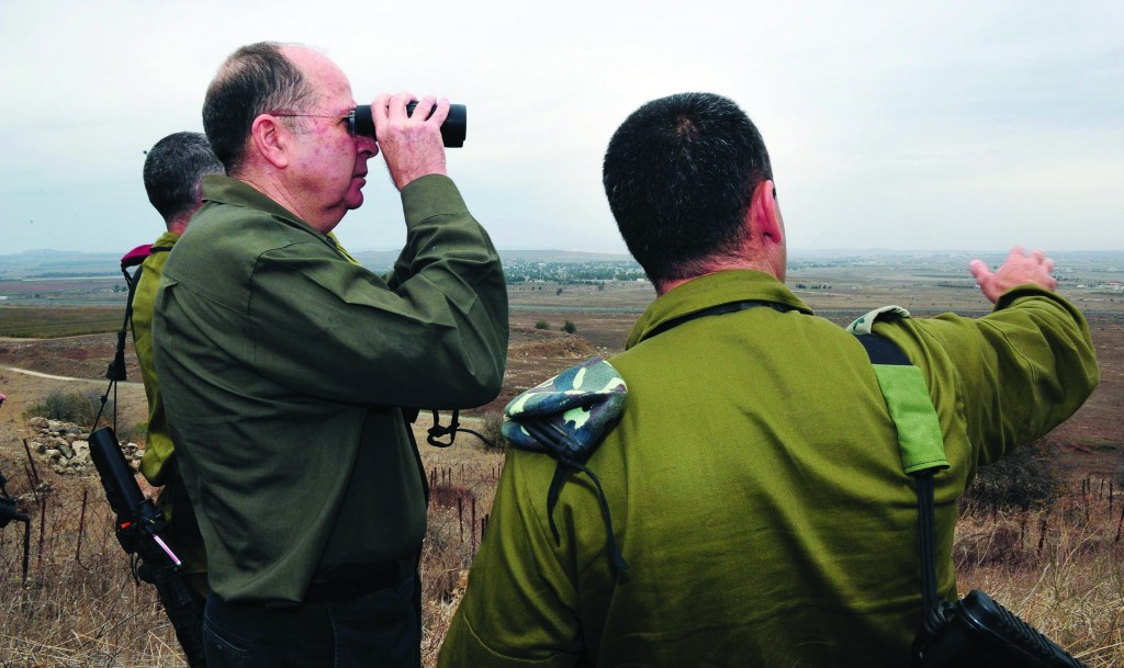 Israeli Defense Minister Moshe Yaalon uses binoculars to survey Syrian territory from the Golan heights on a recent tour. (Ariel Hermoni/Ministry of Defense/Flash 90)