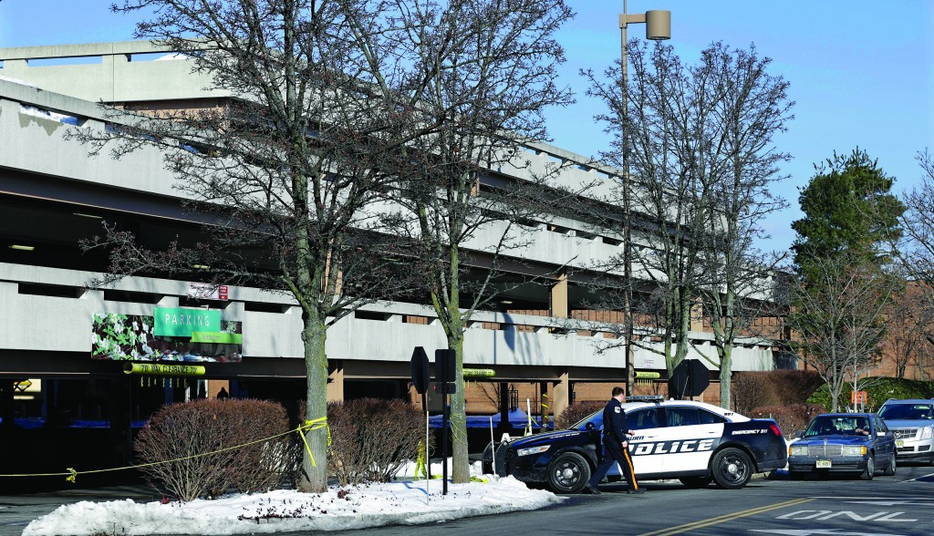 A police officer arrives at a parking garage at The Mall in Short Hills, N.J., Monday where a fatal carjacking took place the day before, in which Dustin Friedland (B), 30, was killed. (AP Photo/Mel Evans)