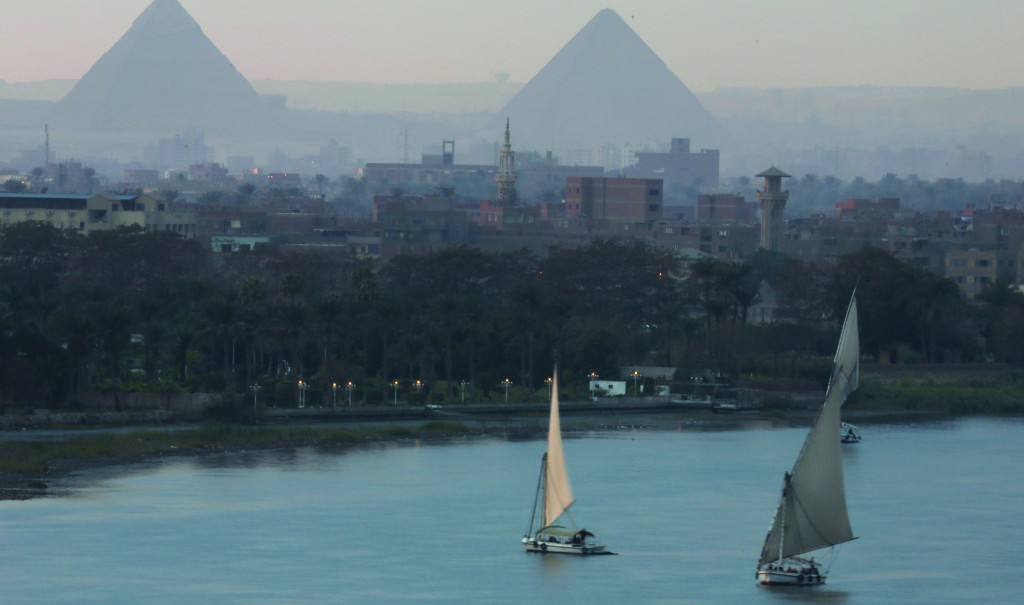 Egyptians enjoy traditional Nile cruises in front of the historical site of Giza Pyramids in Cairo, Egypt, on Tuesday. Political instability and the lack of security are two factors in the dramatic decline in the number of tourists visiting Egypt. (AP Photo/Amr Nabil)