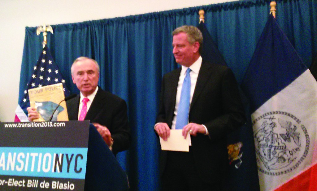 William Bratton displays a book he says influenced his policing from a young age as mayor-elect Bill de Blasio looks on in Red Hook, Thursday. (Colin Campbell/Politicker)