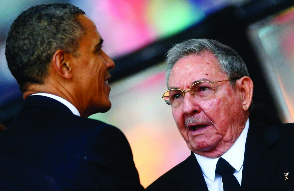 U.S. President Barack Obama (L) greets Cuban President Raul Castro before giving his speech at the memorial service for late South African President Nelson Mandela at the First National Bank soccer stadium, in Johannesburg Tuesday. (REUTERS/Kai Pfaffenbach)