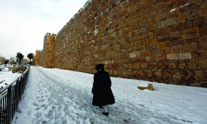 In this photo taken by a non-Jewish photographer, a Yid makes his way through the snow, Shabbos, along the walls of the Old City of Yerushalayim. (REUTERS/Baz Ratner)