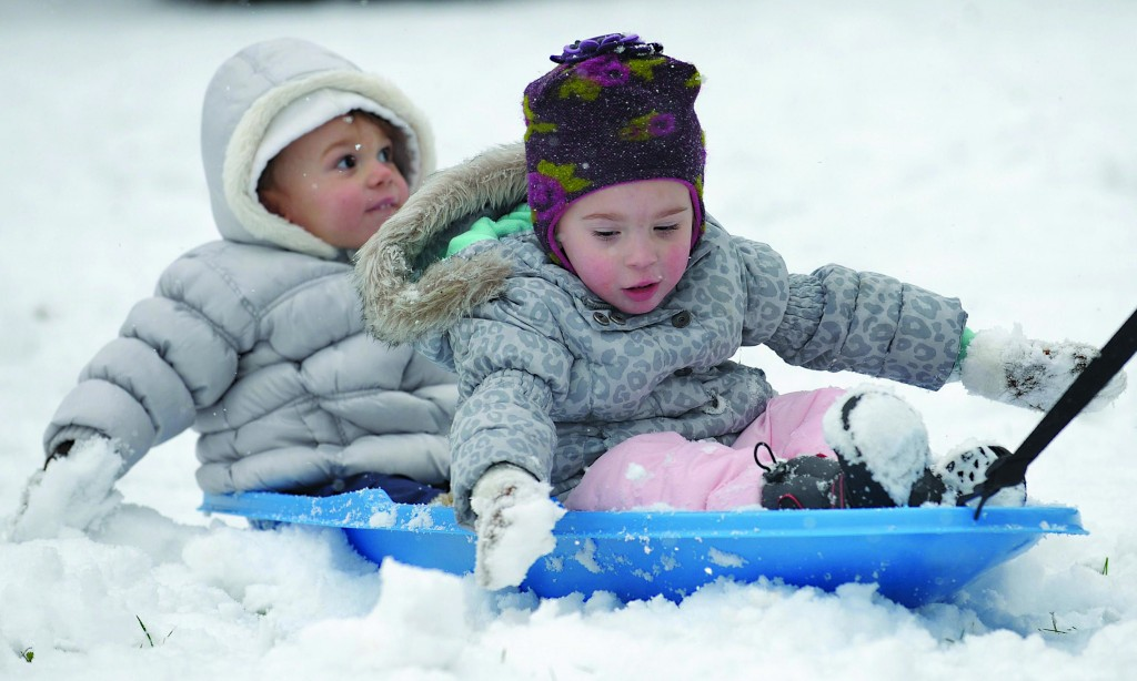 The Scardelli siblings, 1- and 2-years-old, ride on a sled in the yard of their home in Phillipsburg, NJ, Tuesday.
