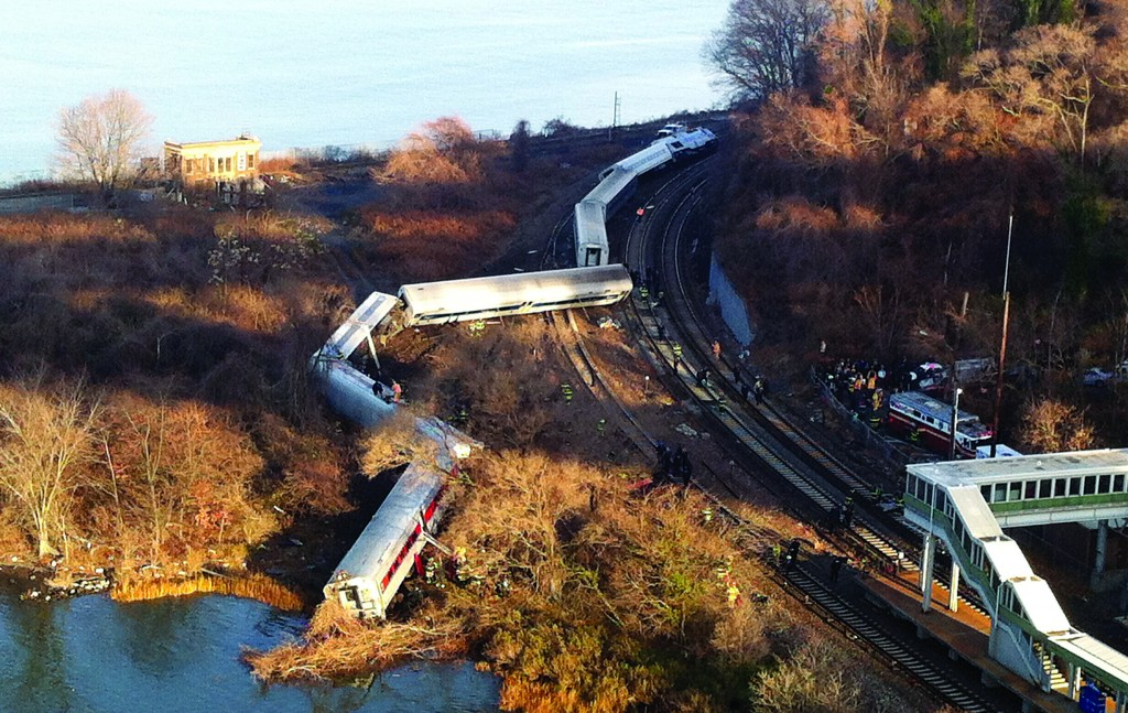 Rail cars are scattered after a Metro-North train derailment in the Bronx on Sunday killed four and injured more than 60 riders. (AP Photo)