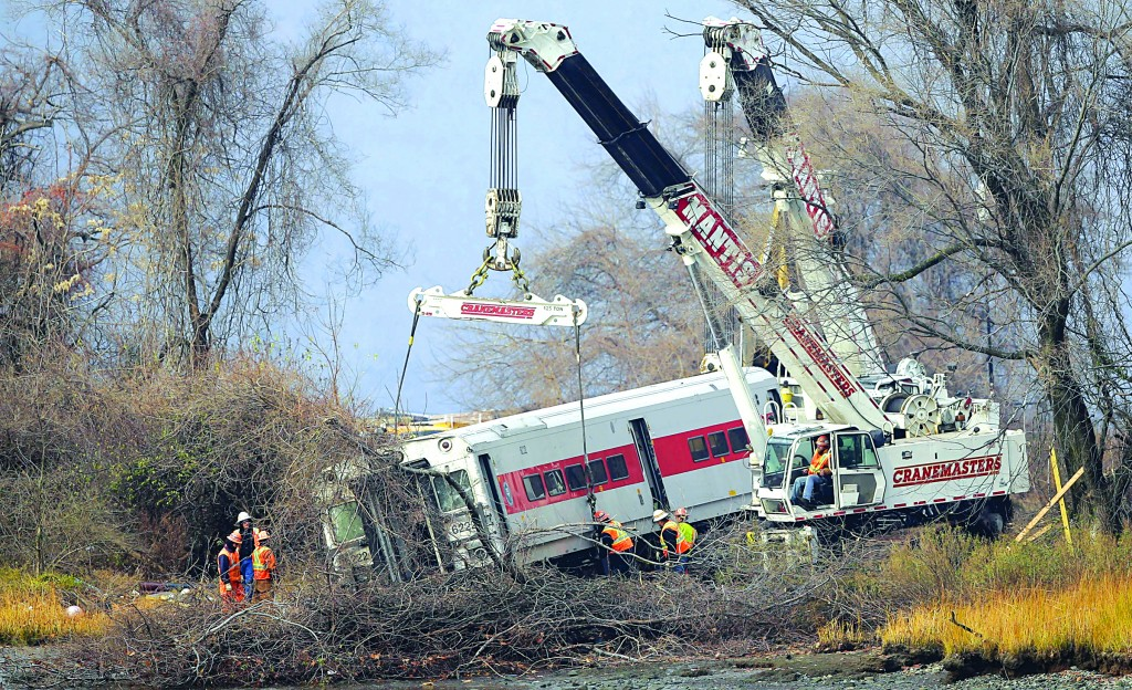 Cranes salvage the last car from the Metro-North commuter train on Monday. (AP Photo/Seth Wenig)