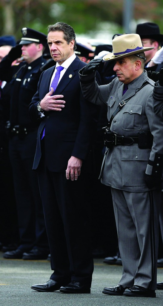 Gov. Andrew Cuomo, (L), and State Police Superintendent Joseph D'Amico stand as the casket of David Cunniff passes on Friday. (AP Photo/Mike Groll)