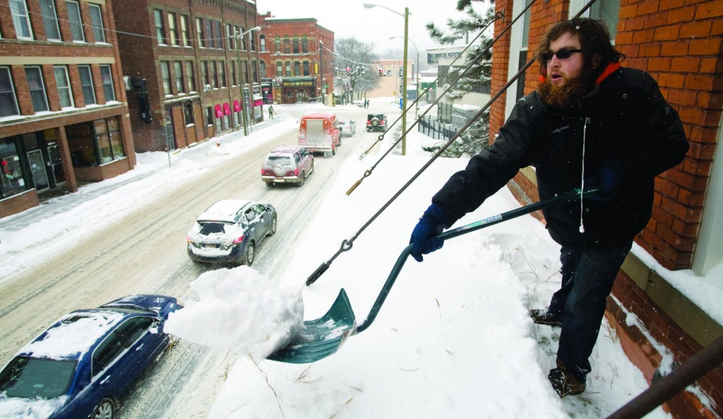 Chris Grubb, of Oneonta, N.Y., shovels snow off a roof overhanging the sidewalk Tuesday. (AP Photo/|The Oneonta Daily Star, Benjamin Patton)