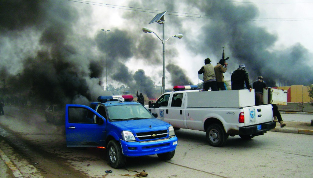 In this January 1, 2014, file photo, al-Qaida fighters patrol in a commandeered police truck passing burning police vehicles in front of the main provincial government building, in Fallujah. The global terror network al-Qaida is positioning itself as defending the Sunni community against Shiite-dominated governments across Syria, Lebanon and Iraq. (AP Photo, File)