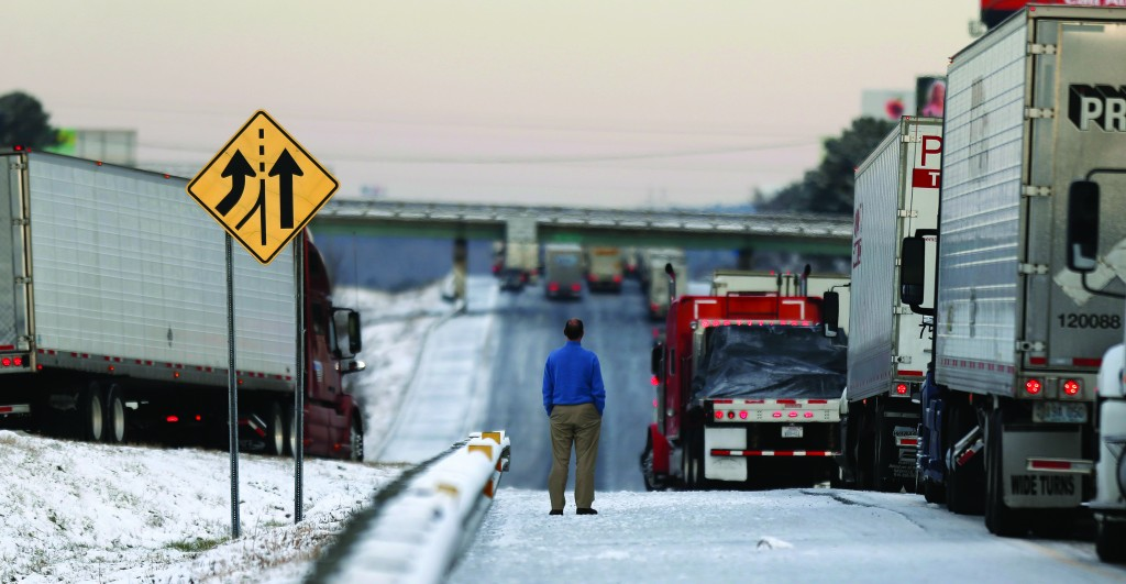 A man stands on the frozen roadway as he waits for traffic to clear along Interstate 75 Wednesday, in Macon, Ga.  (AP Photo/John Bazemore)