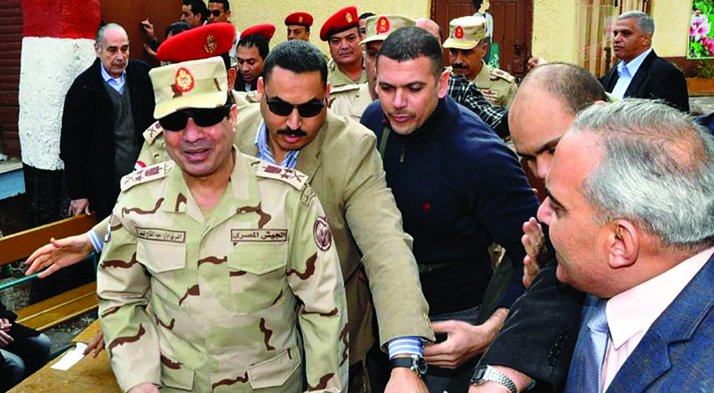 Defense Minister Gen. Abdel-Fattah el-Sisi (L) visits a polling site in the Heliopolis neighborhood of Cairo, Egypt, on the first day of voting in the constitutional referendum. (AP Photo/Egyptian Defense Ministry)