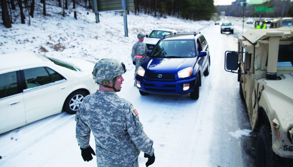 Georgia National Guardsman Command Sgt. Maj. Buddy Grisham is joined by fellow troops as they help people get their stranded cars out of the snow in Atlanta, Georgia Thursday. (REUTERS/Chris Aluka Berry)