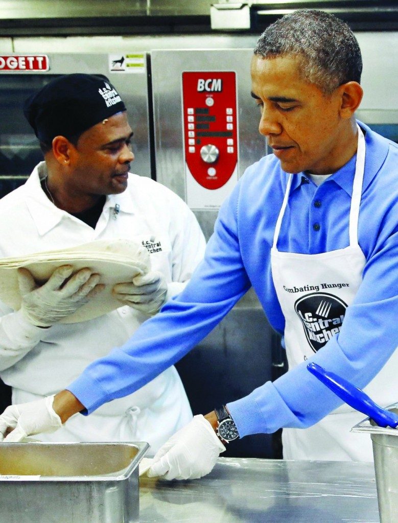 U.S. President Barack Obama (R) fills burritos as he and his family volunteer at the DC Central Kitchen charity in honor of the Martin Luther King Jr. holiday, in Washington. (REUTERS/Jonathan Ernst)