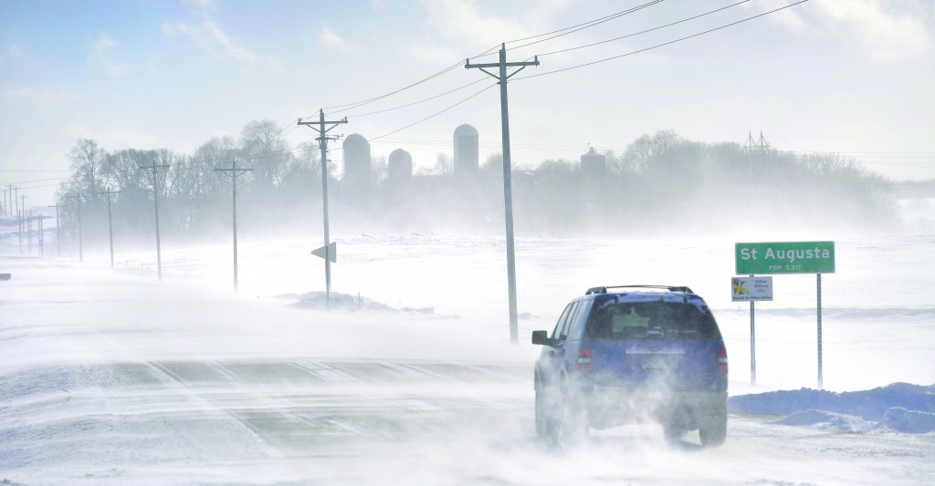 An SUV ventures past the St. Augusta, Minn., city limits sign on Stearns County Road 136 in near white-out conditions Sunday afternoon, south of St. Cloud, Minn. (AP Photo/St. Cloud Times, Kimm Anderson)