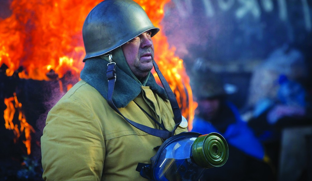 An opposition supporter stands next to a burning tire at a barricade in central Kiev, Ukraine, Thursday. (AP Photo/Darko Bandic)