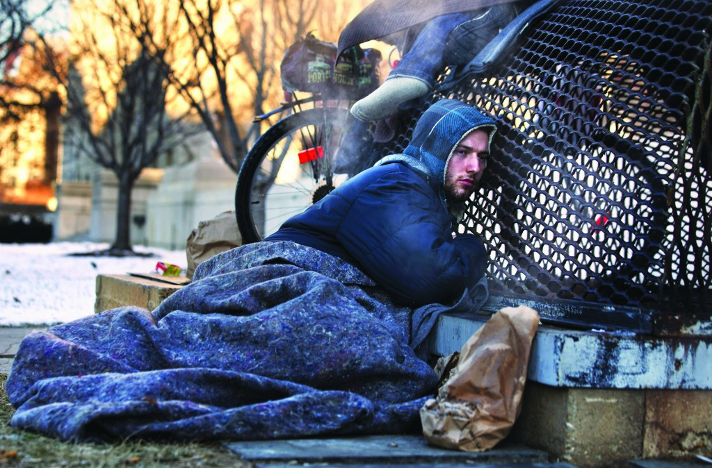 Nicholas Simmons, 20, of Greece, N.Y., warms himself on a steam grate blocks from the Capitol, during frigid temperatures in Washington, Saturday. (AP Photo/Jacquelyn Martin)