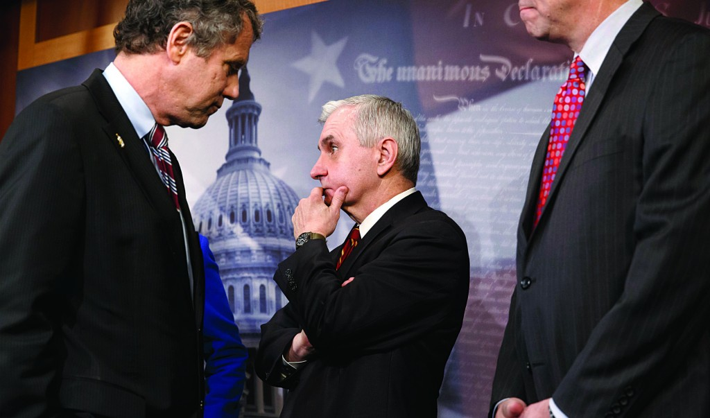 Sen. Jack Reed (D-R.I.) (C), stands with Sen. Sherrod Brown (D-Ohio) (L) and Sen. Jeff Merkley (D-Ore.) (R), during a news conference on Capitol Hill in Washington, Tuesday, after legislation to renew jobless benefits for the long-term unemployed unexpectedly cleared an initial Senate hurdle. (AP Photo/J. Scott Applewhite)