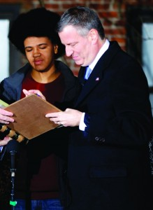 Mayor Bill de Blasio signs the oath of office shortly after midnight early Wednesday, as his son Dante looks.