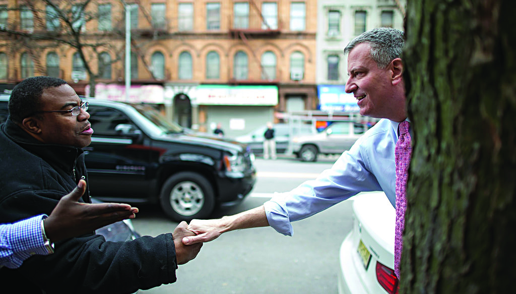 Mayor Bill de Blasio greets passersby in Harlem on Monday. (Rob Bennett/City Hall)