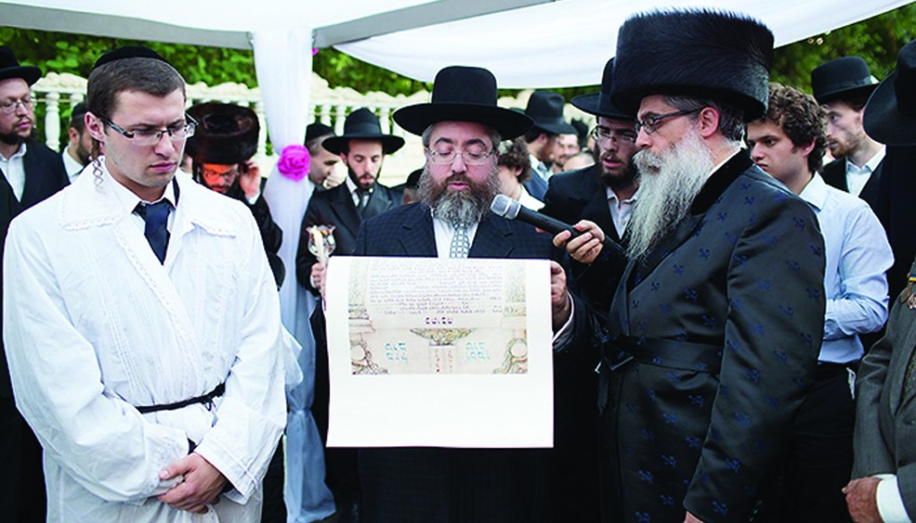 At a chasunah in Kiev last week, Rabbi Mordechai Shlomo Bald, Chief Rabbi of Lvov, reads the kesubah as Rabbi Yaakov Bleich, Chief Rabbi of Ukraine, watches (right).