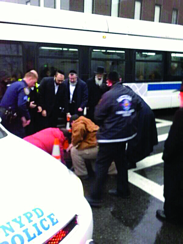 Hatzolah and Verizon workers on Tuesday morning attempt to pull Moshe Altman out of an open manhole on 13th Ave. and 49th Street. (News Breakers)