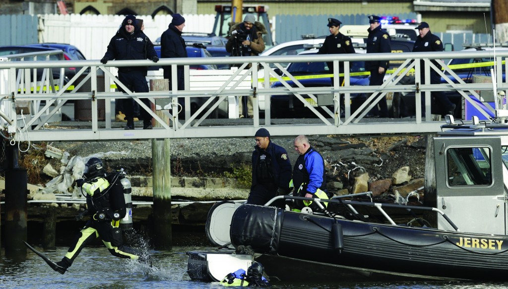 A workers in dive gear, left, jumps into the water while trying to recover Mark Pych's vehicle. (AP Photo/Julio Cortez)