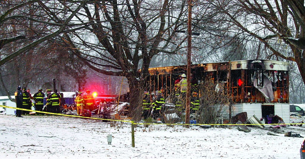 Firefighters on Sunday investigate a fatal fire in a mobile home in Penfield, N.Y. that killed eight-year-old Tyler Doohan as he tried saving his handicapped grandfather. (AP Photo/Rochester Democrat and Chronicle, Jamie Germano)