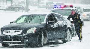 Newark Police Officer Paul Keld helps a stuck driver along Paper Mill Road, Tuesday, get up the hill as traffic behind piles up in Newark, Delaware. (AP Photo/The Wilmington News-Journal, Suchat Pederson)