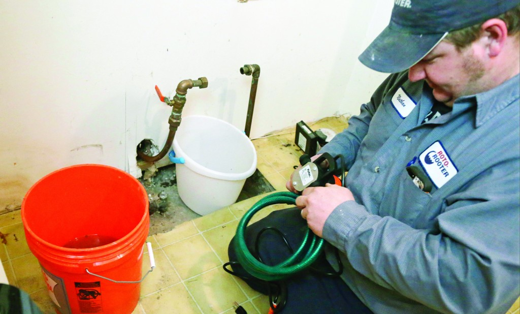 Plumber Nate Petersen prepares a pump to shoot water into the incoming city water line, left pipe, that was frozen Thursday, at a south Minneapolis home. (AP Photo/Jim Mone)