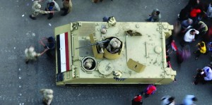 Egyptians walk around an armored personnel carrier parked at a rally marking the third anniversary of the 2011 uprising in Tahrir Square in Cairo, Egypt. (AP Photo/Amr Nabil)