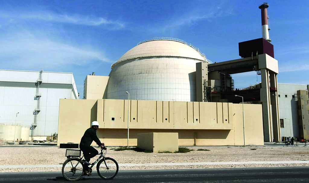 A worker rides a bicycle in front of the reactor building of the Bushehr nuclear power plant, just outside the southern city of Bushehr. (AP Photo/Mehr News Agency, Majid Asgaripour, File)