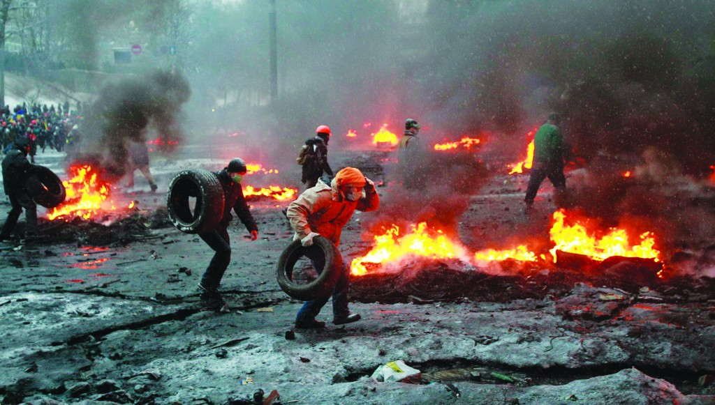Pro-European protesters carry tires to burn during clashes with riot police in Kiev Wednesday. (REUTERS/Gleb Garanich)