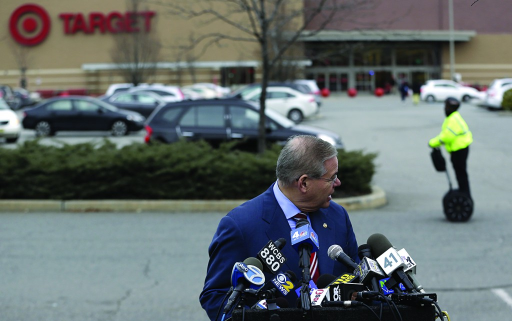 A security guard rides by on a personal moving device as U.S. Sen. Robert Menendez looks back during a recent news conference outside of a Target store, in Jersey City, N.J. (AP Photo/Julio Cortez)