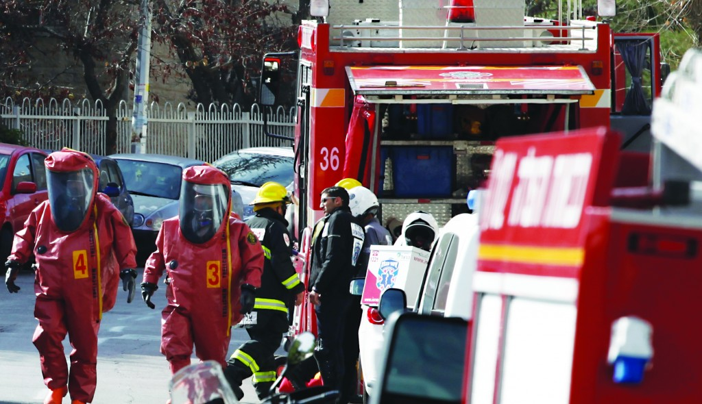 Rescue workers seen at the scene of the apartment where two children died of poisoning and two others were in serious condition, on Wednesday. (Flash 90)