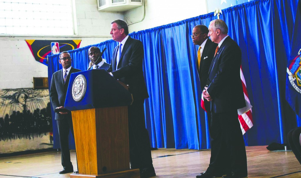 Mayor Bill de Blasio speaks Thursday in Brownsville, Brooklyn, on the deal to end the stop-question-and-frisk legal fight. To the right are Police Commissioner William Bratton and city counsel Zach Carter. (Reuters/Eric Thayer)