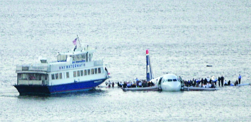 Passengers stand on the wings of a U.S. Airways plane as a ferry pulls up to it after it crash-landed in the Hudson River on Jan. 15, 2009. (Reuters/Brendan McDermid)