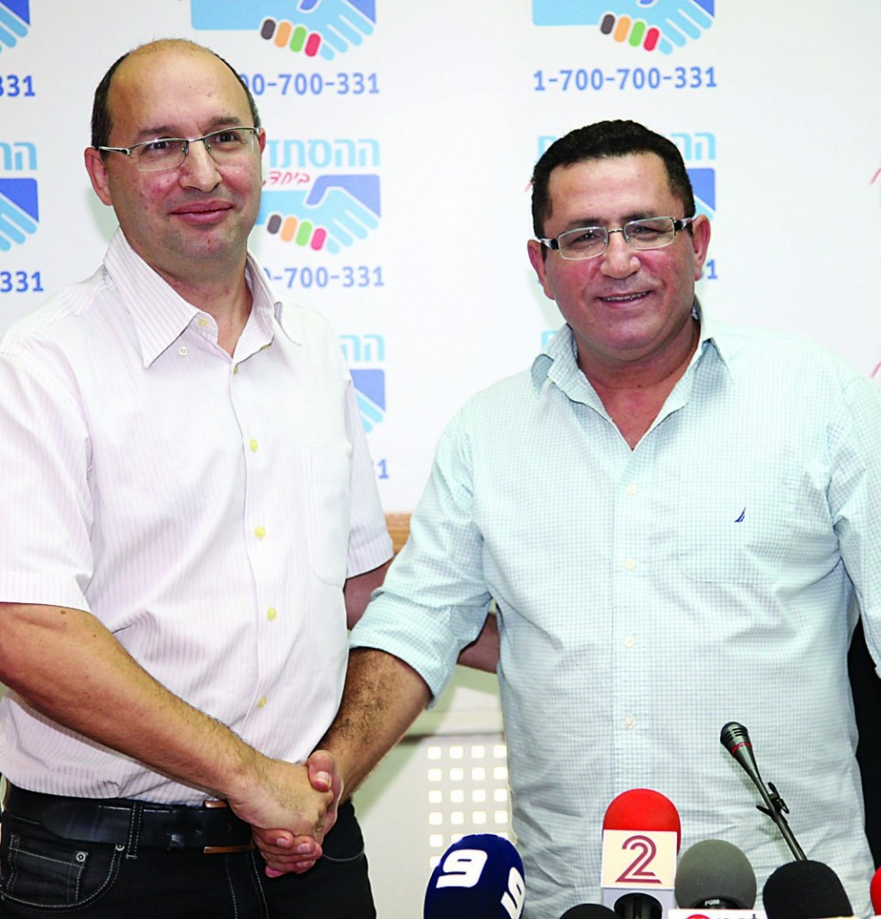 Outgoing chairman of the Histadrut Labor Federation Ofer Eini (R) shakes hands with Avi Nissankoren, whom he has designated to replace him. (Gideon Markowicz/Flash90)