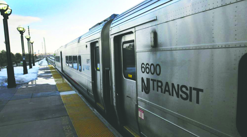 A NJ Transit train, its now-expired logo emblazoned on its side, pulls into a station in New Jersey.