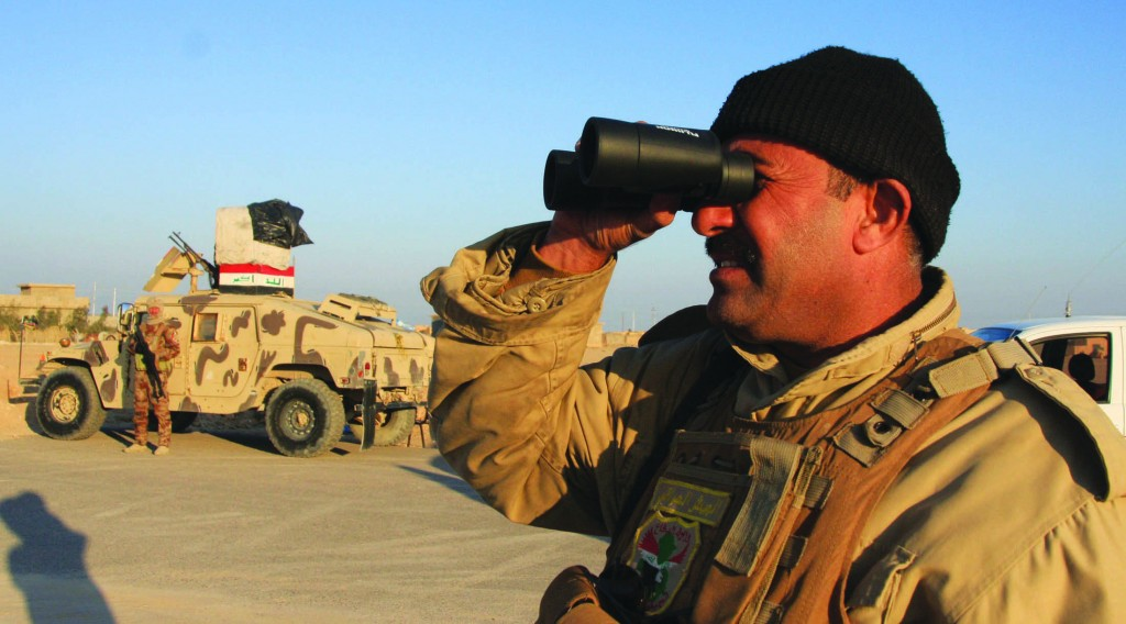 An Iraqi soldier uses binoculars at a checkpoint in Ein Tamarm, a town some 40 km (25 miles) west of Kerbala, Iraq, Tuesday. (REUTERS/Mushtaq Muhammed)