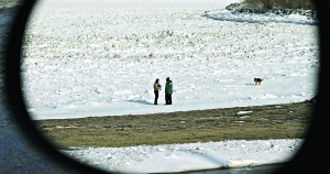Two people stand on a frozen Lake Erie Wednesday, in a photo taken from the rearview mirror of a vehicle.