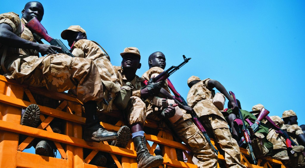 Some of hundreds of government soldiers who boarded trucks as they prepare to travel towards the frontline to reinforce forces near the town of Bor, which is currently held by rebels, in South Sudan, Monday, Jan. 13, 2014. Despite the appearance of diplomatic progress, the conflict seems set to continue. (AP Photo/Jake Simkin)