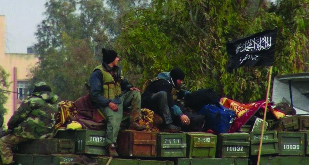 This citizen journalism image provided by Edlib News Network, ENN, an anti-Bashar Assad activist group, which has been authenticated based on its contents and other AP reporting, shows rebels from al-Qaida affiliated Jabhat al-Nusra, as they sit on a truck full of ammunition, at Taftanaz air base, that was captured by the rebels, in Idlib province, northern Syria. (AP Photo/Edlib News Network, ENN, File)