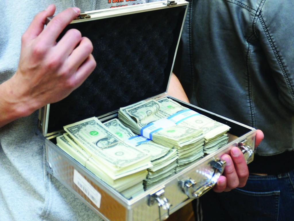 University of Utah student Luke Mughal holds a briefcase full of one-dollar bills to pay his tuition at the University of Utah campus in Salt Lake City, Utah. (Salt Lake Tribune, Steve Griffin)